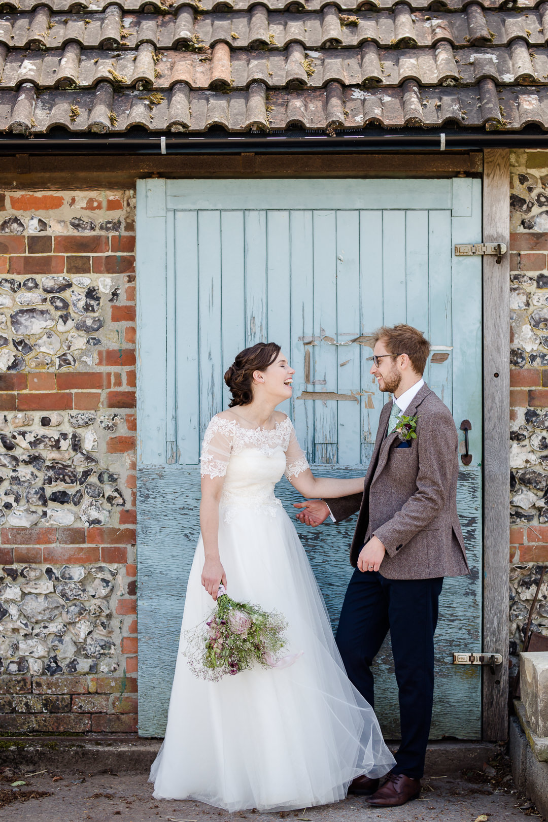 bride and groom laughing in front of rustic door