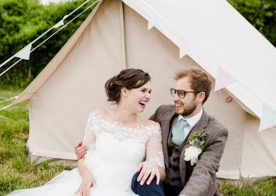 bride and groom relaxing by a tent on their wedding day