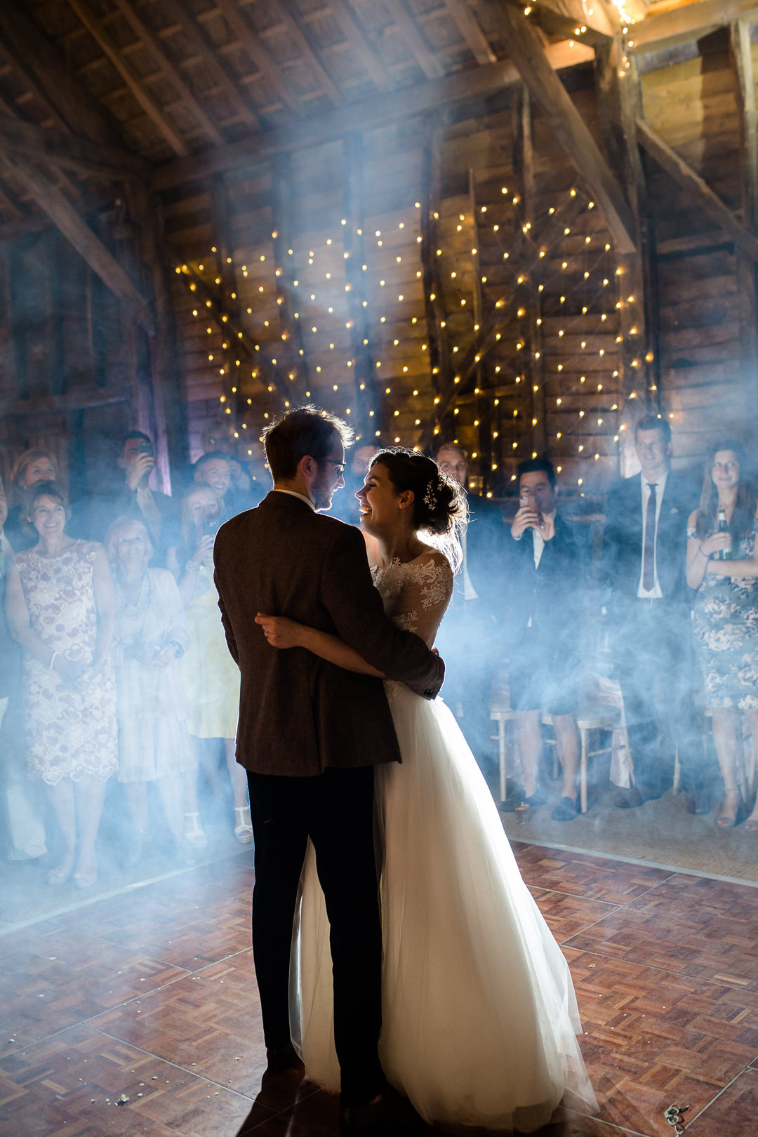 bride and groom having their first dance with smoke machine and fairy lights in a barn