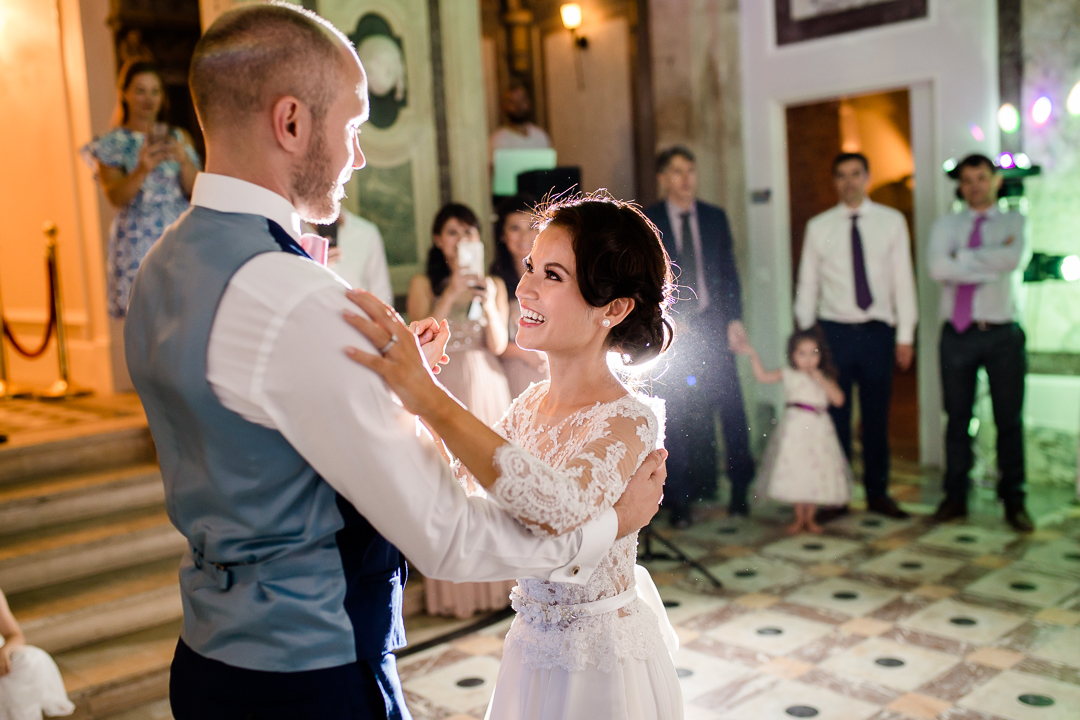 bride looks lovingly at groom during their first dance at chateau bouffemont, paris, France image