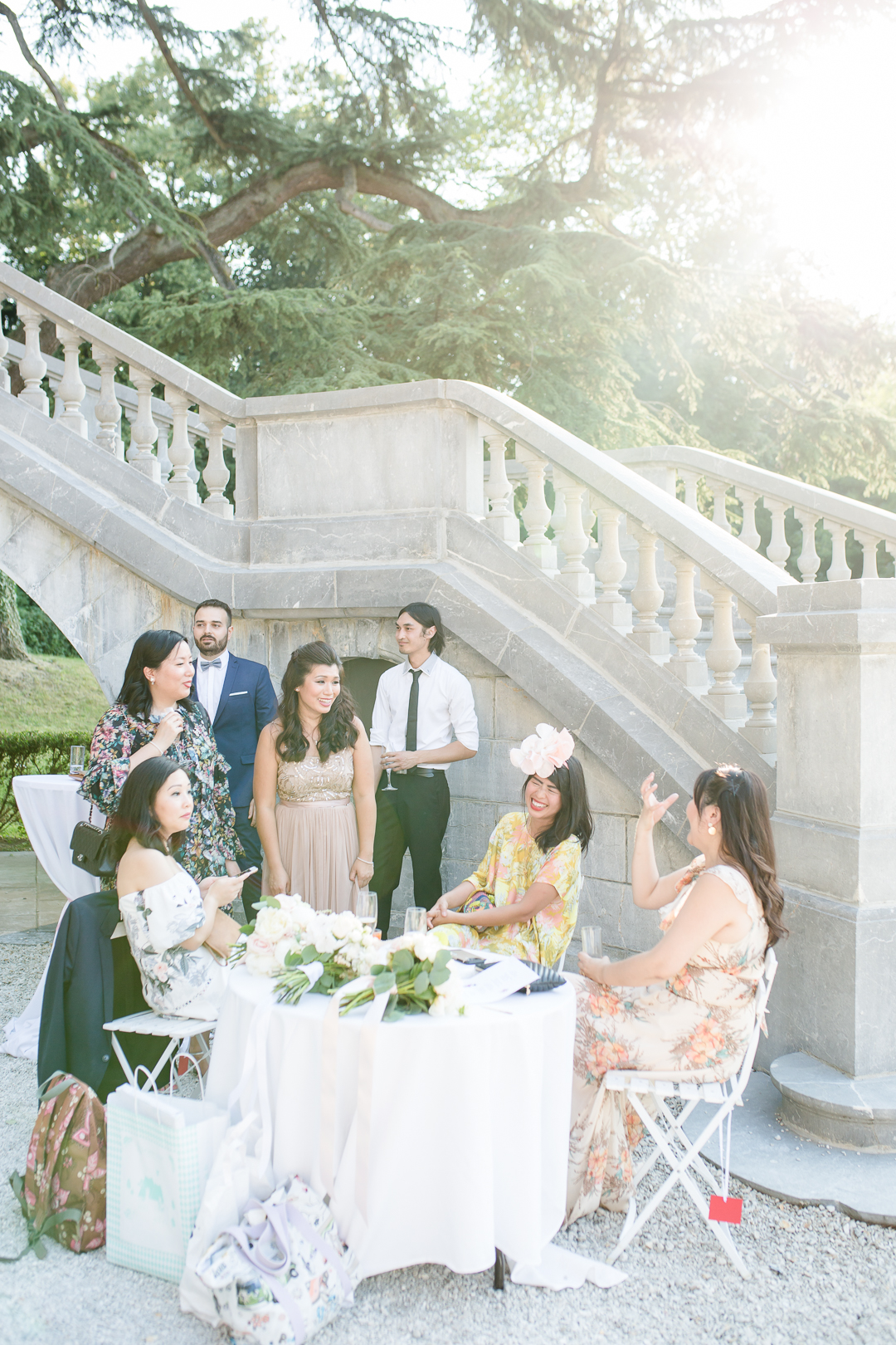 group of friends chatting around a table during a drinks reception at a chateau bouffemont wedding image