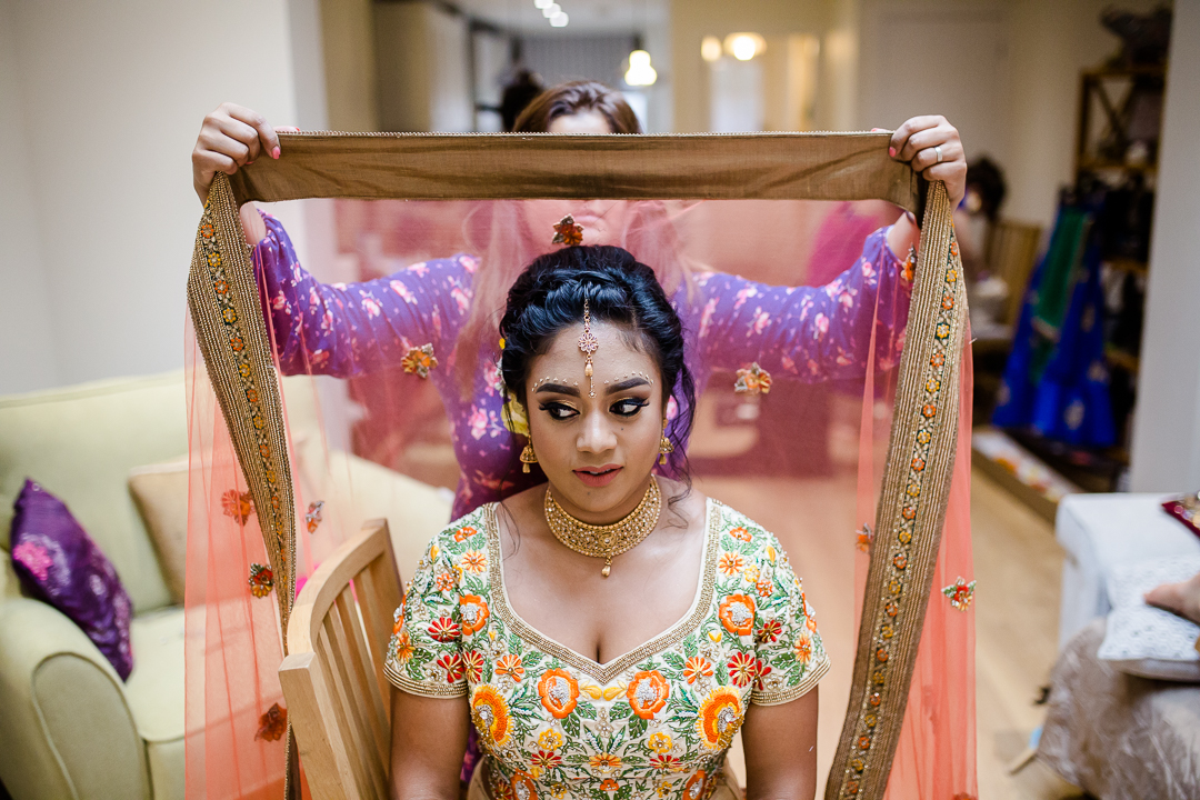 Asian bride has her veil placed for her Hindu wedding