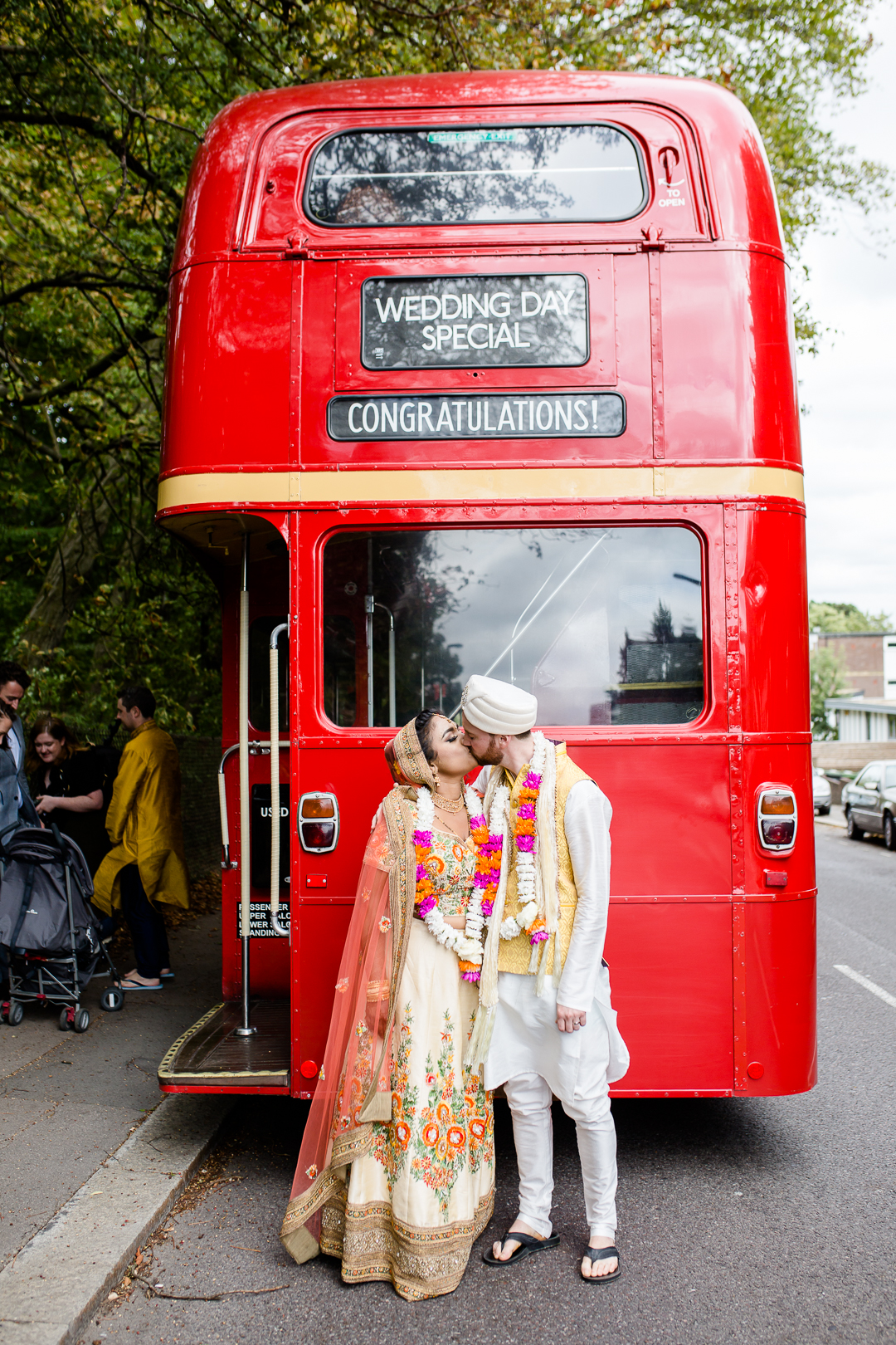 Bride and groom in Hindu wedding sari & pyjama share a kiss by London route master bus