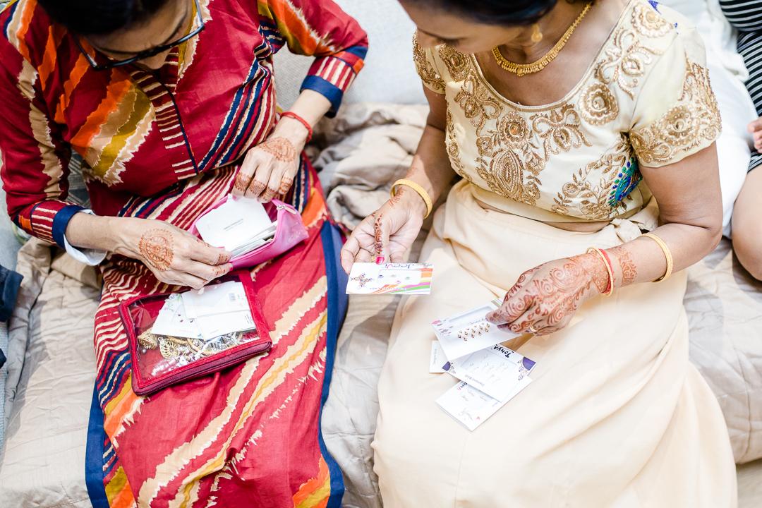 Asian women in saris choosing bindis for a Hindu wedding