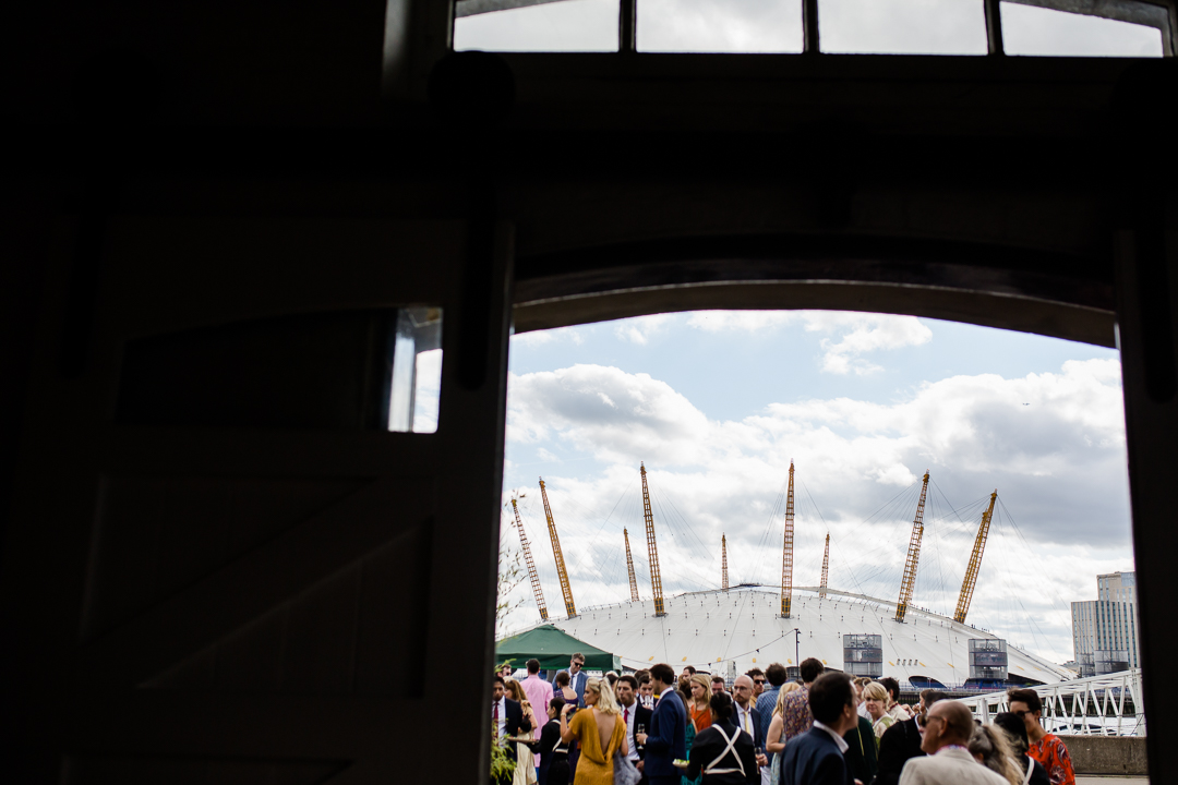 guests mingling during a drinks reception on the dockside at trinity bouy wharf london wedding venue with the millenium dome in the background.