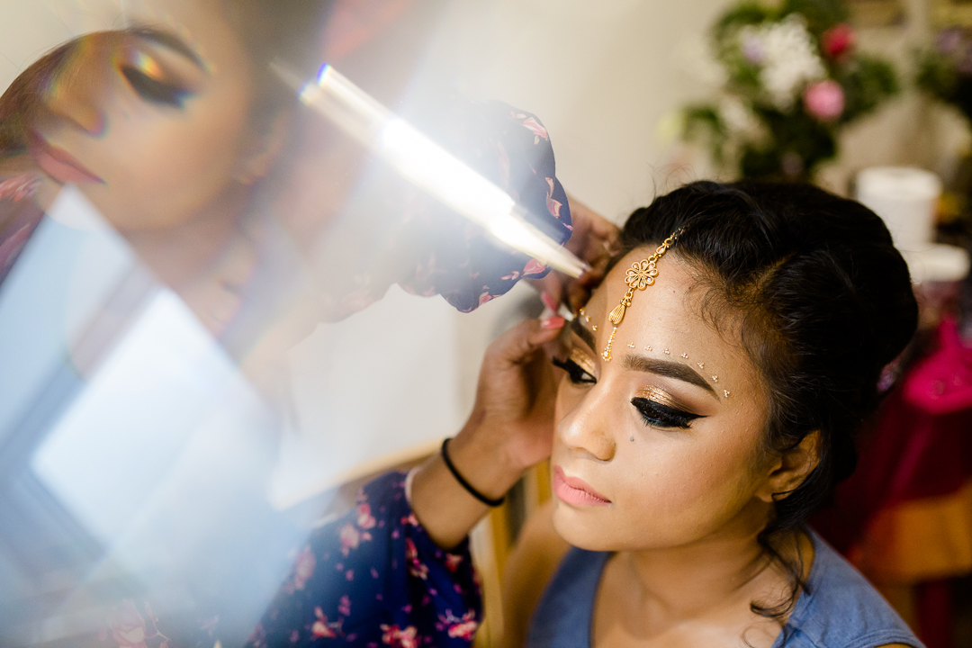 Asian bride preparing for her Hindu wedding ceremony is adorned with bindis and maang tikka