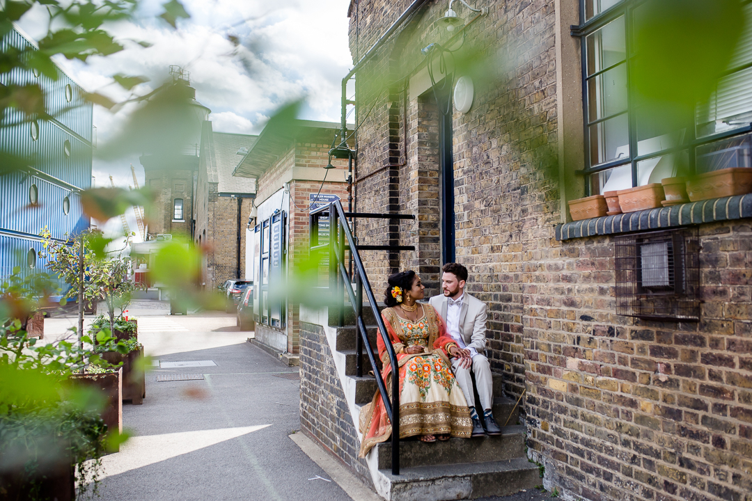 bride and groom sit on some steps in an urban area near Trinity Bouy Wharf wedding venue London