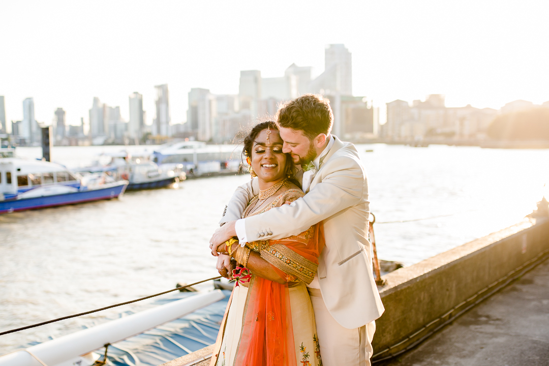 Bride and groom embrace in the sunset on the dockside at Trinity Bouy Wharf wedding venue London