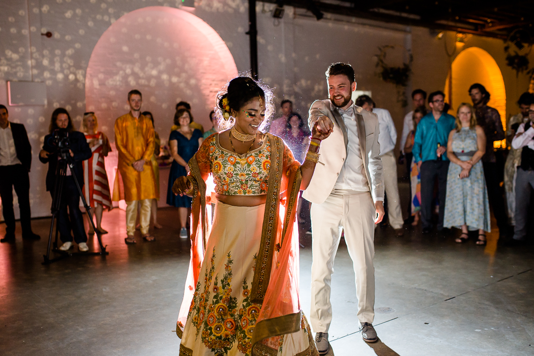 bride in sari and her groom have their first dance at their wedding at trinity bouy wharf warehouse in London