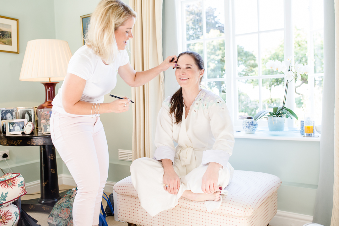 bride getting make up done on wedding morning while sitting on footstool