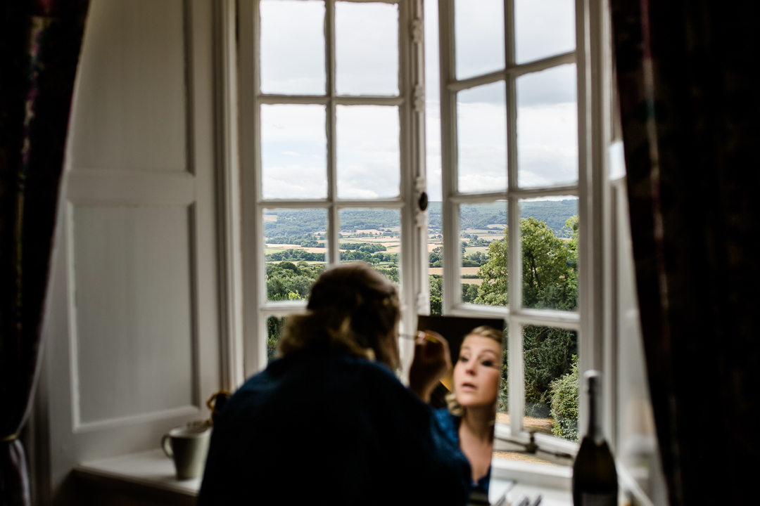 Bride doing make up in the window of Barley Wood House near Bristol