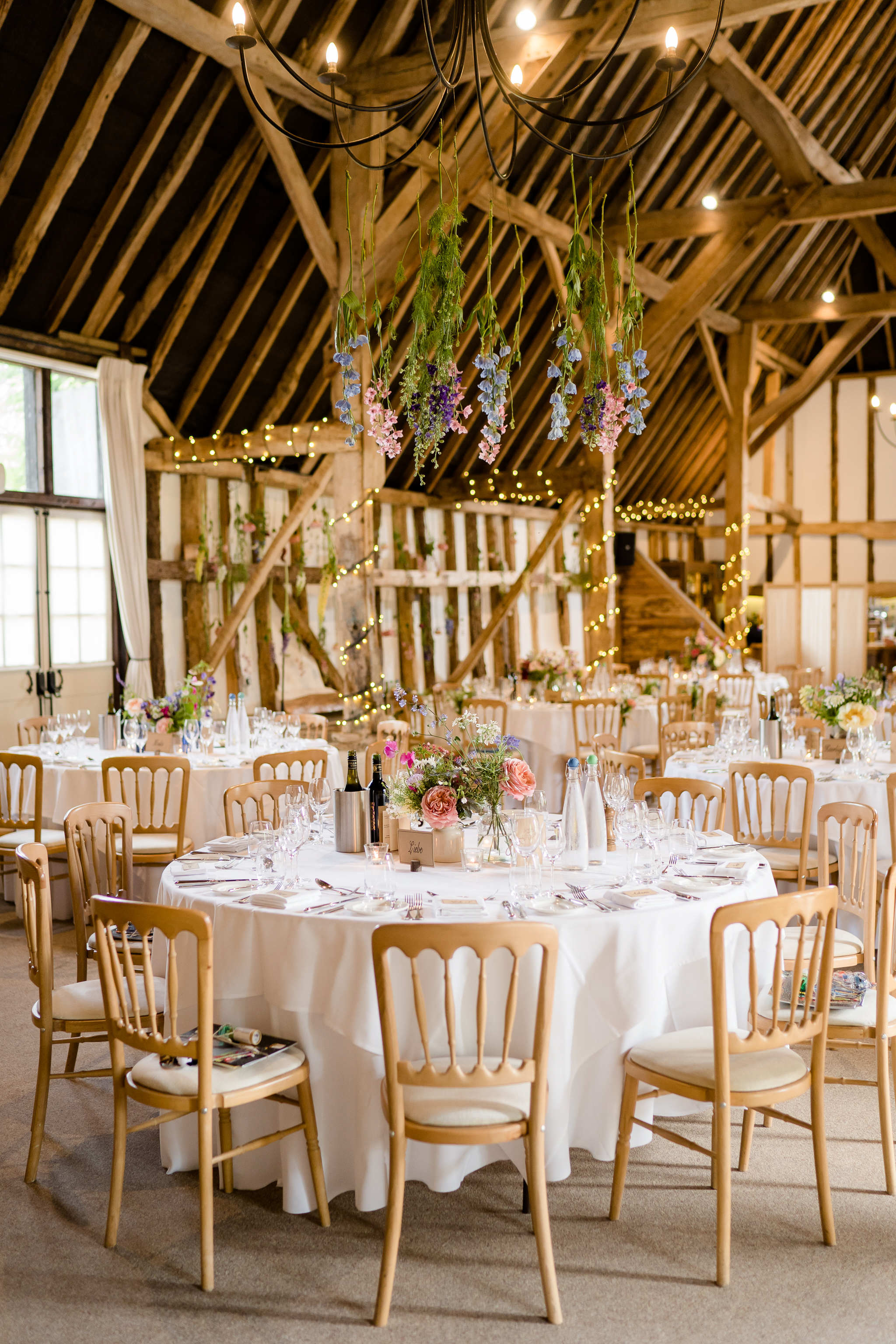 Clock Barn set up for a wedding breakfast with flowers hanging from the chandeliers by The White Horse Flower Company