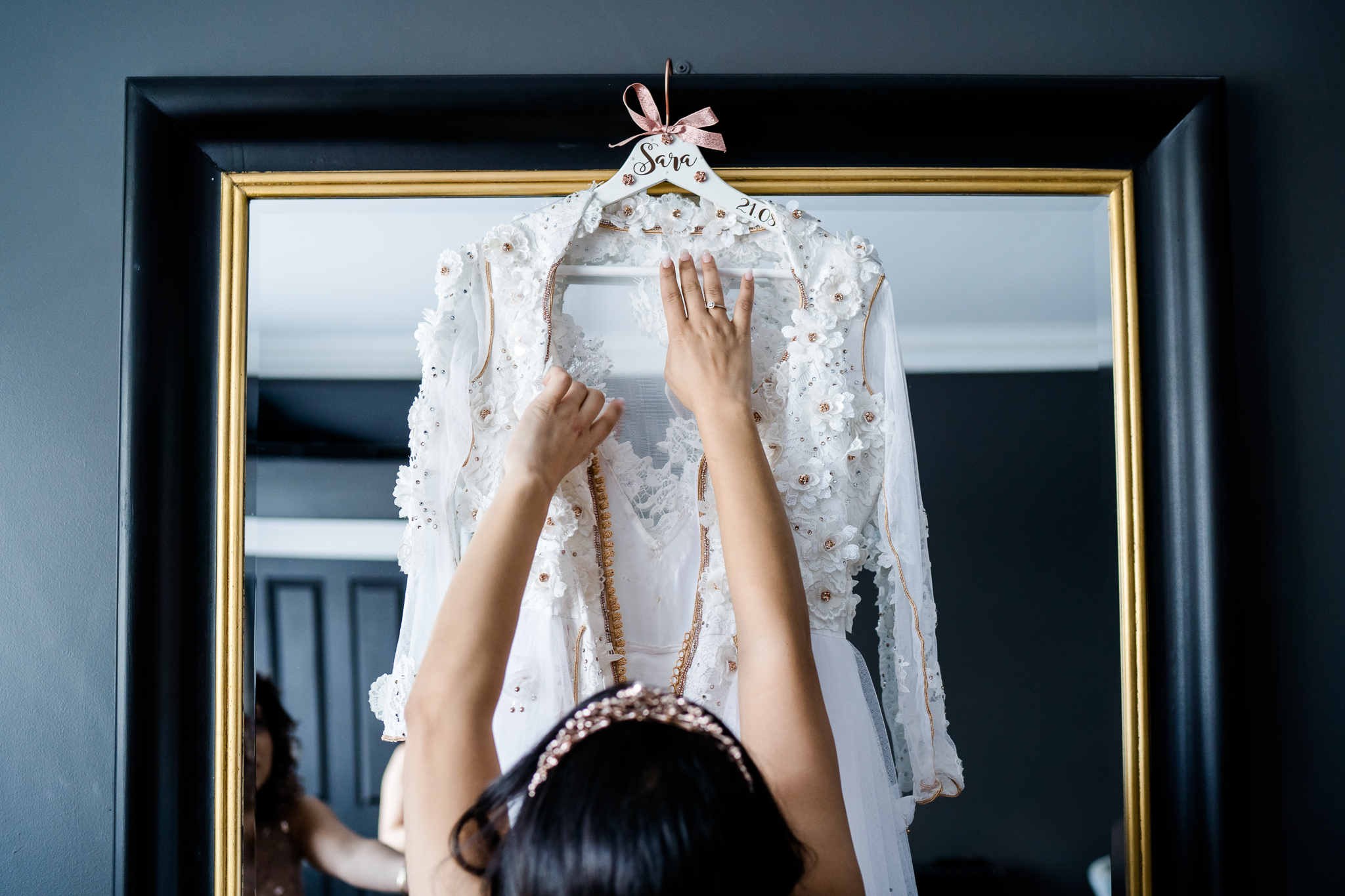 bride reaching for wedding dress at swynford manor, photo by Lydia Stamps Photography