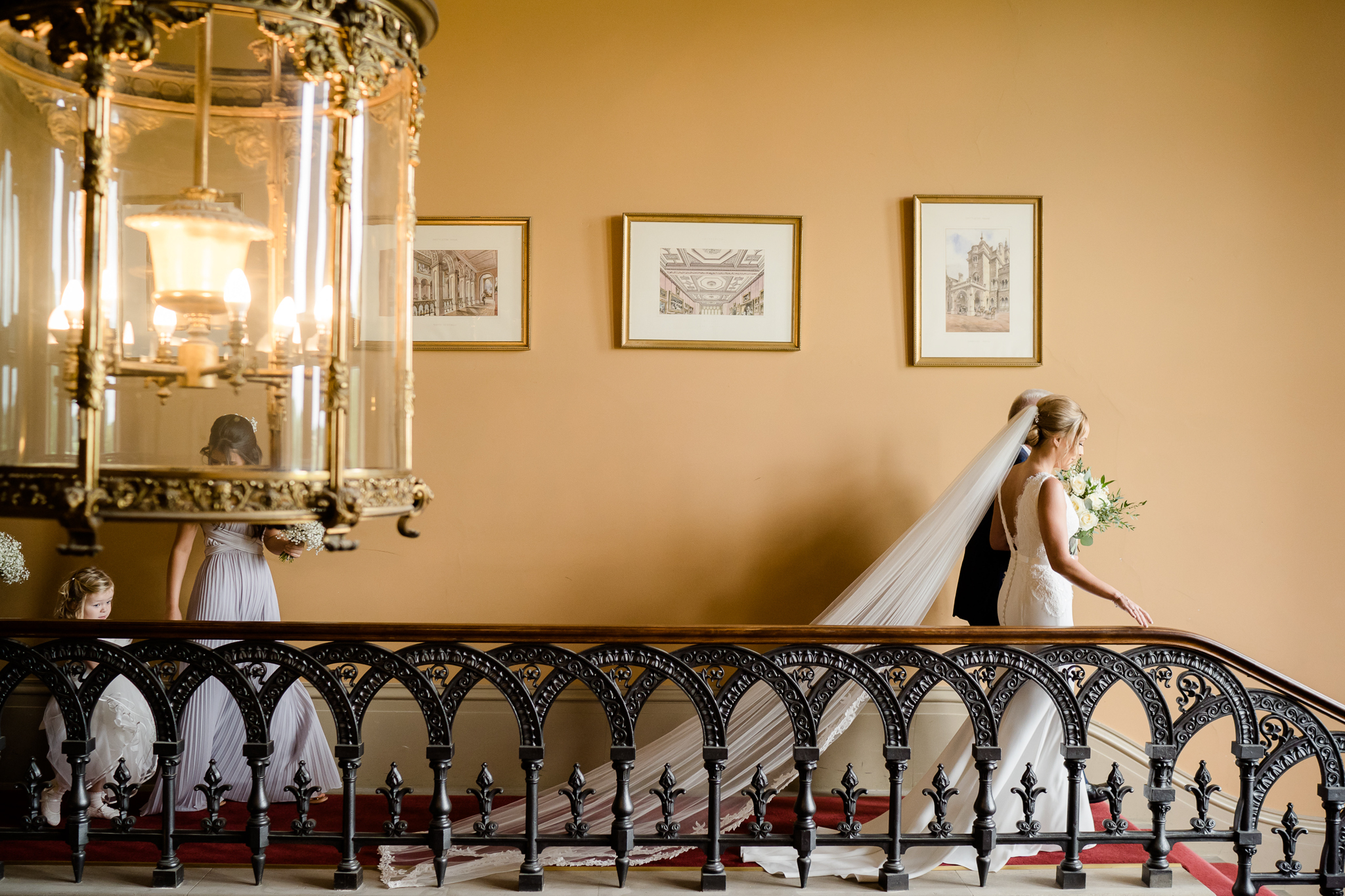 bride walking along the grand stair case at Grittleton House wedding venue in Wiltshire photo by Lydia Stamps Photography