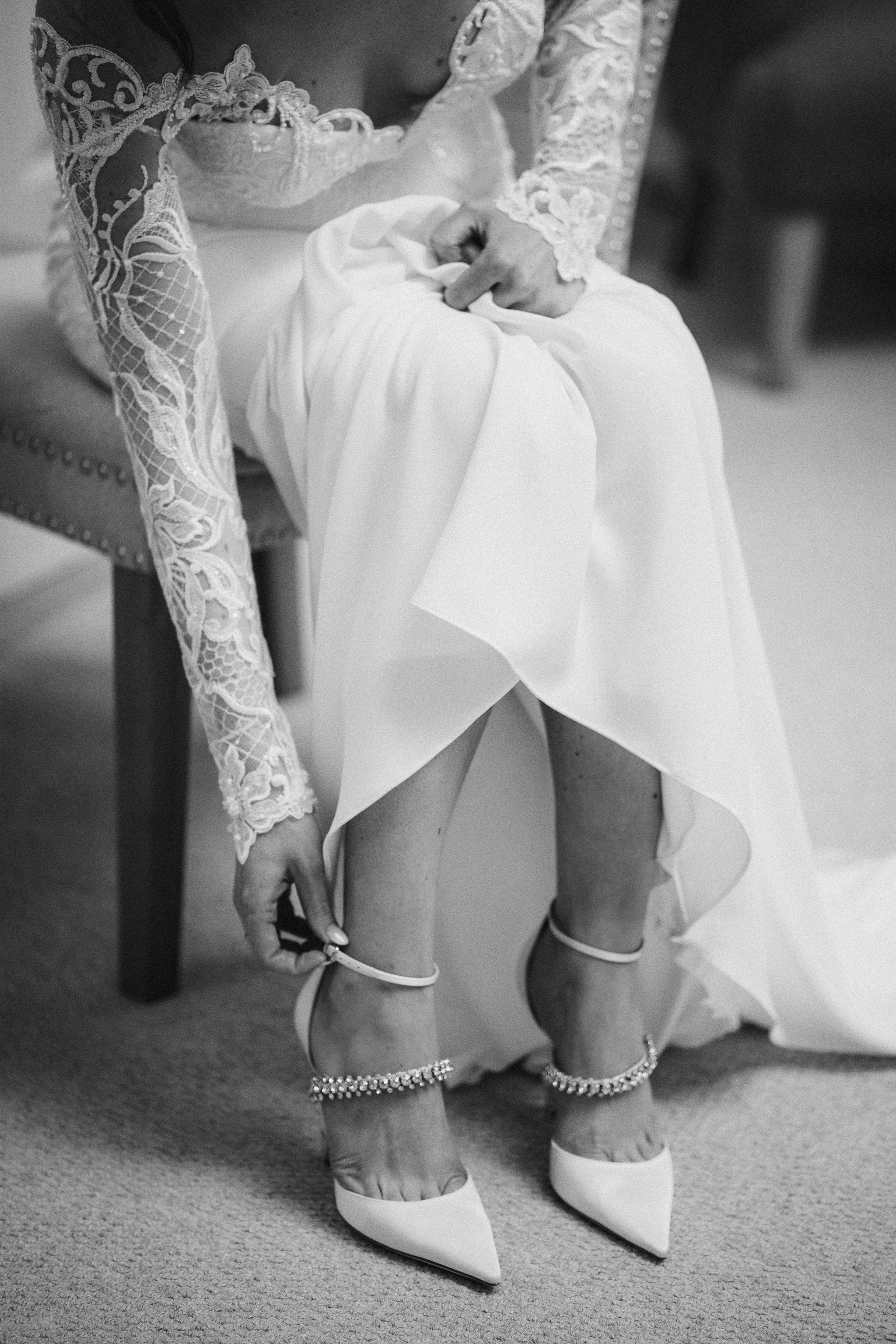 bride adjusting Jimmy Choo wedding shoes photo by Lydia Stamps Photography