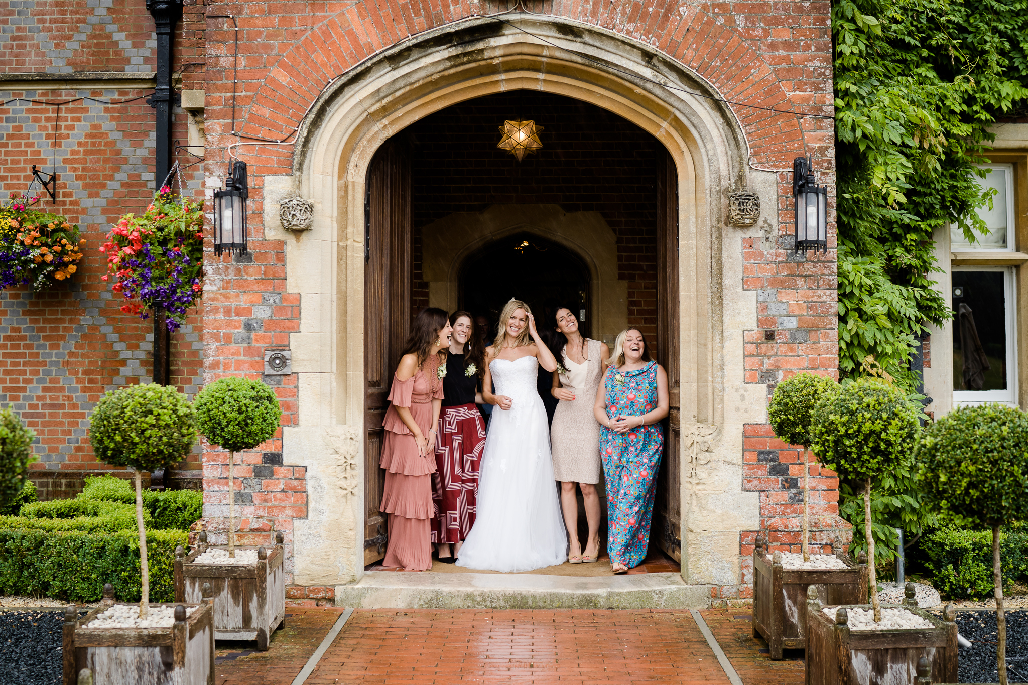 a bride and her friends gathered in the doorway of Burley Manor wedding venue in the new forest