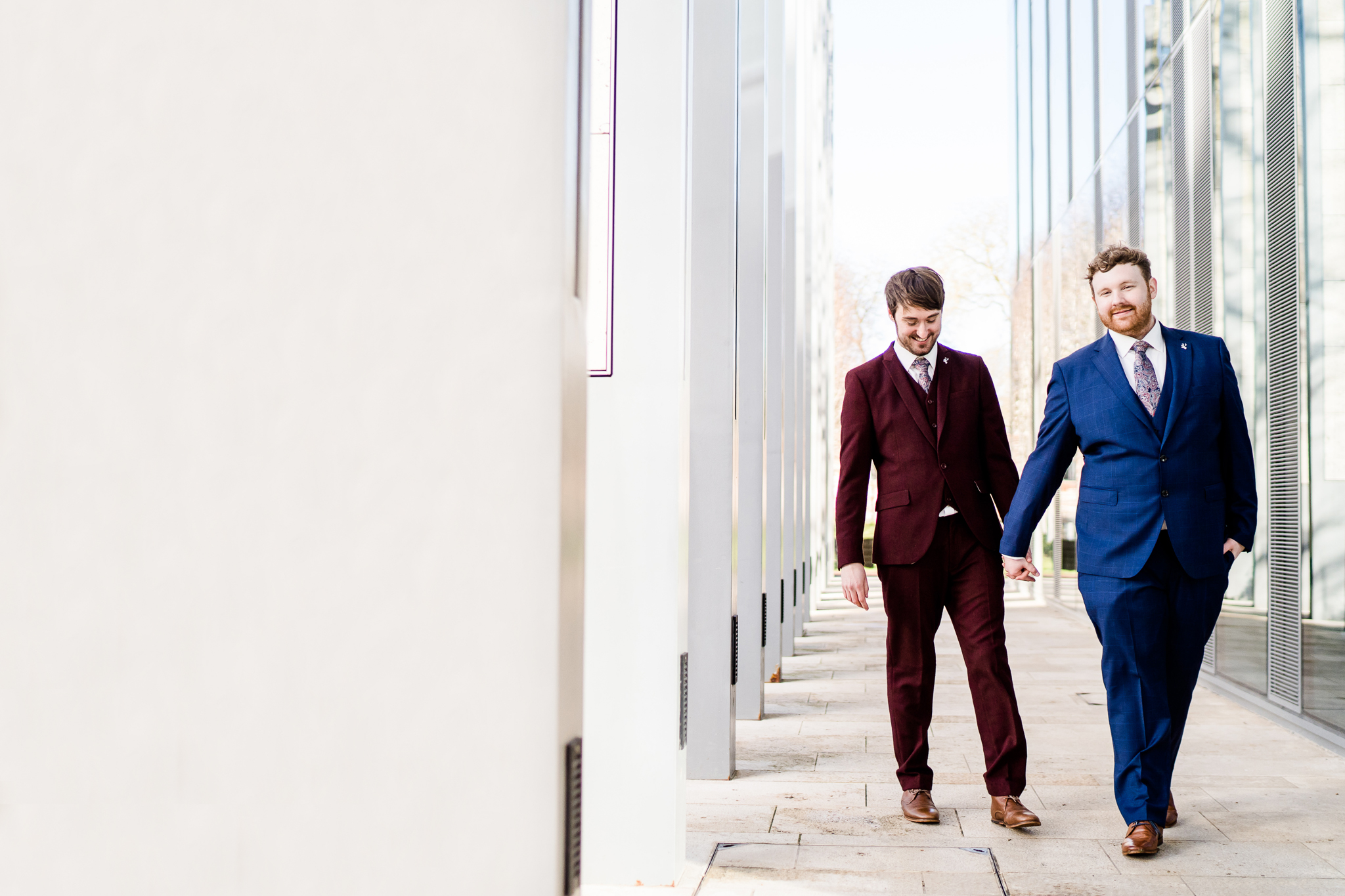 two grooms walk hand in hand at Salisbury registry office