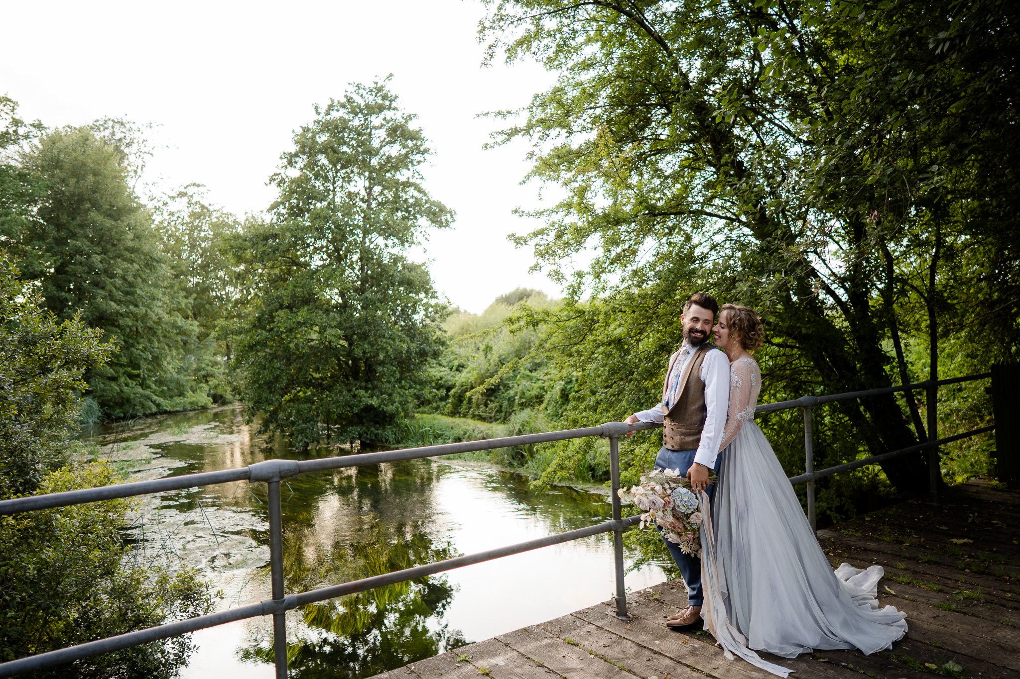 bride and groom stand by the river at the barn at avington wedding venue near winchester