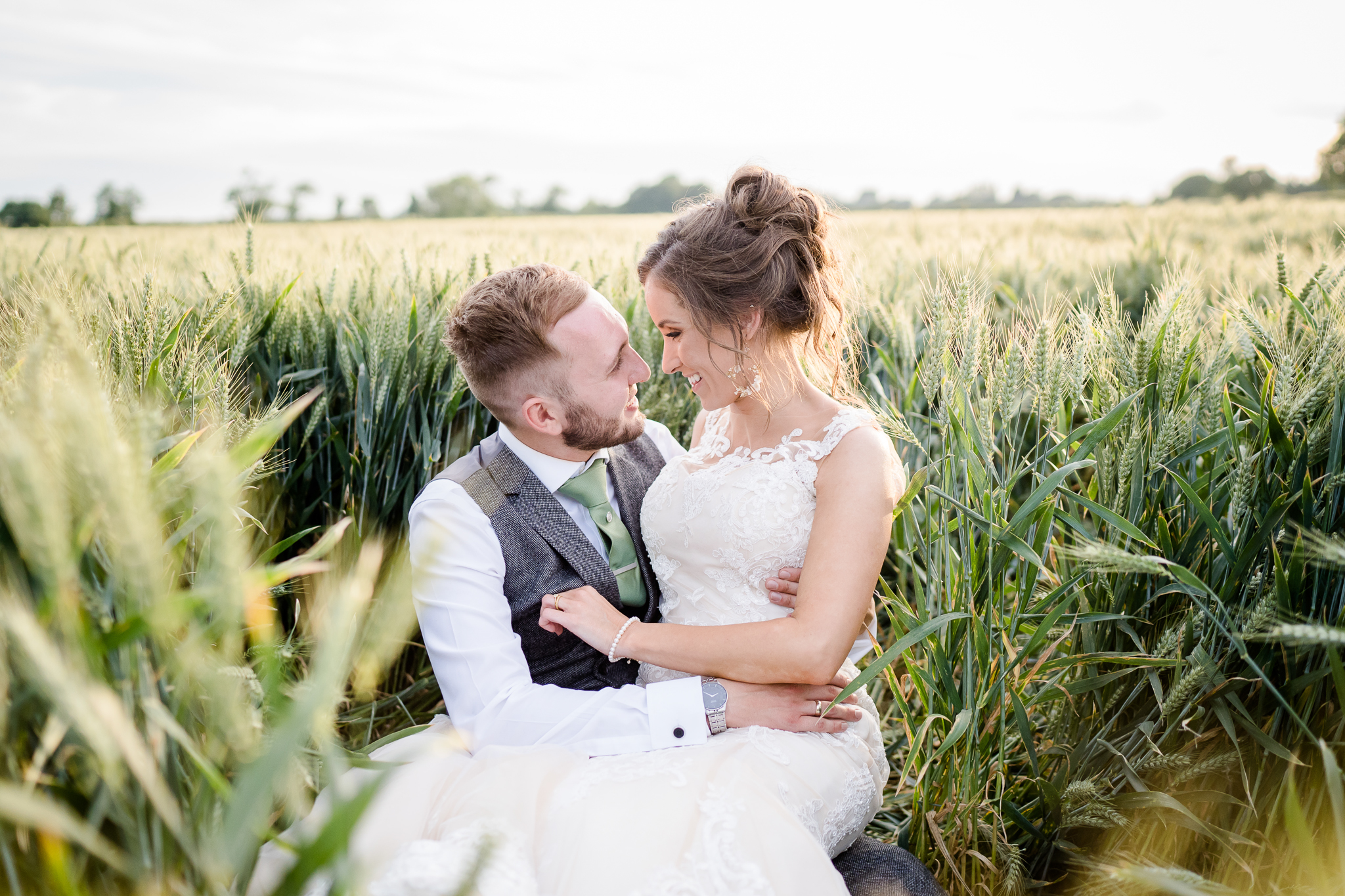 bride and groom sit in cornfield at Southend Barns at sunset