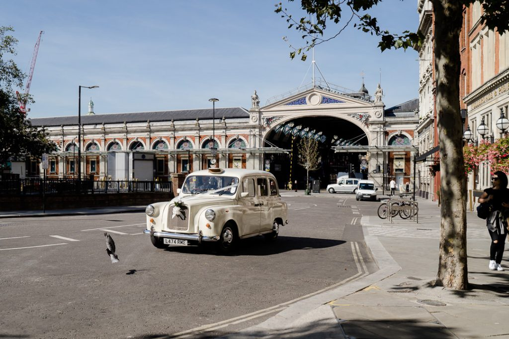 white london taxi for wedding outside Spitalfields market photo by Lydia Stamps Photography