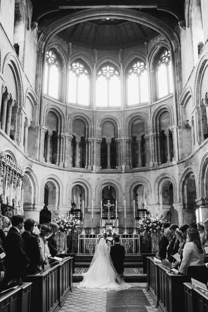 bride and groom are blessed inside St. Bartholomew's Church Spitalfields London photo by Lydia Stamps Photography