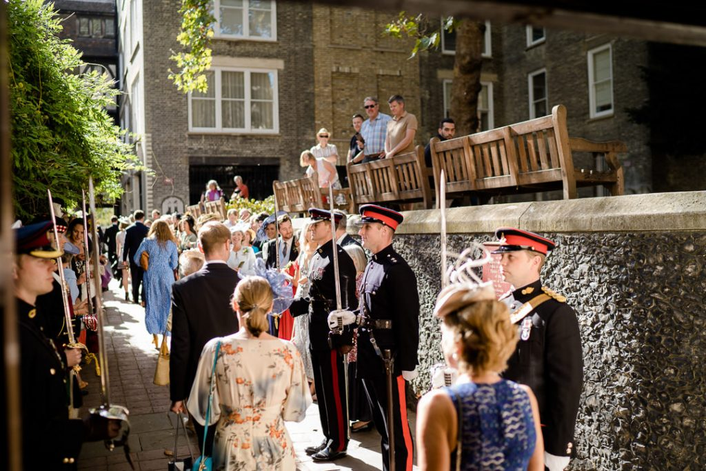 a guard of honour and wedding guests gather outside St. Bartholomew's Church Spitalfields London photo by Lydia Stamps Photography
