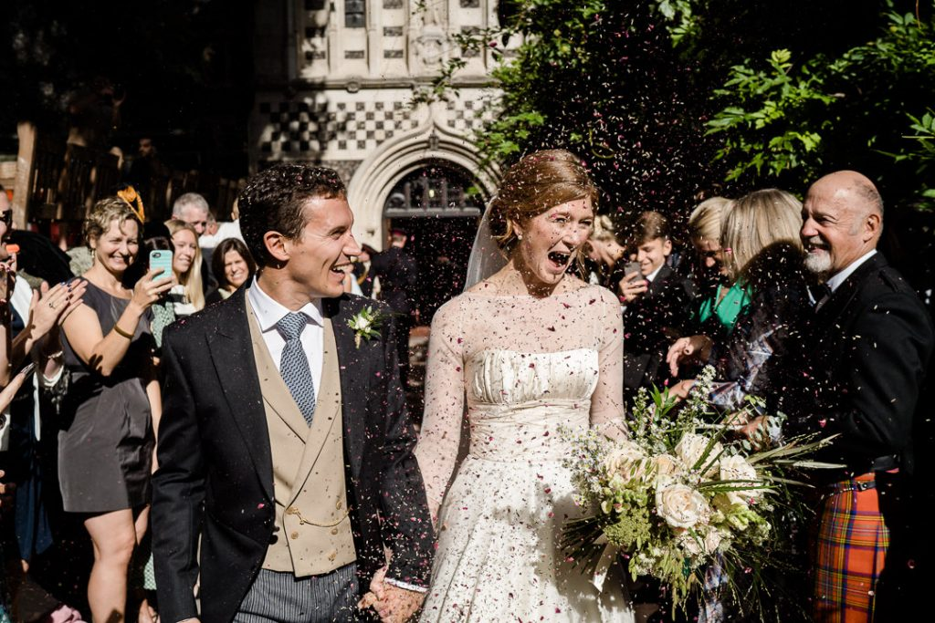 bride and groom exit St. Barts church London Spitafields in confetti photo by Lydia Stamps Photography