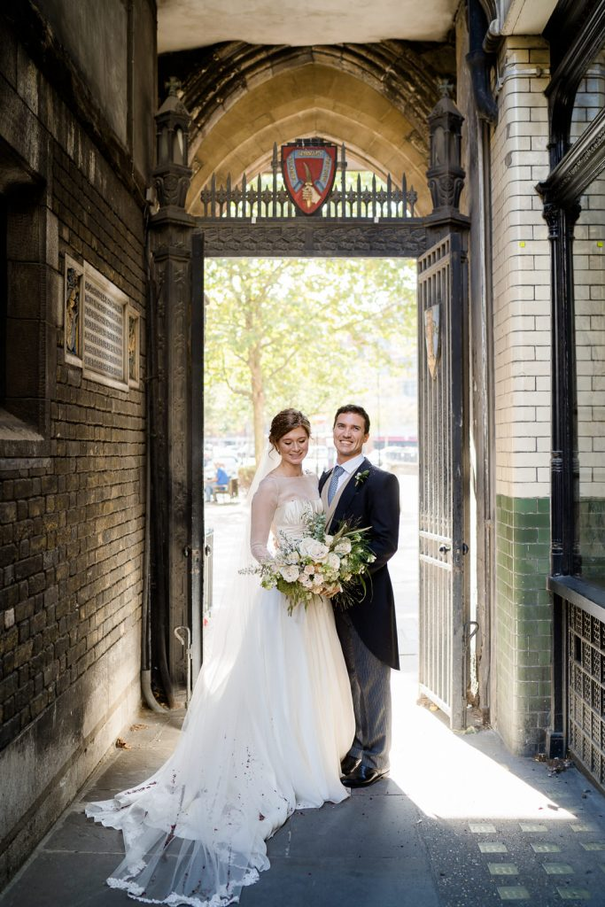 bride and groom in the entrance of St. Barts church Spitalfields London after their wedding ceremony photo by Lydia Stamps Photography