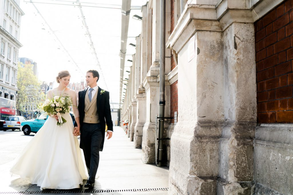 bride and groom walk past Spitalfields market after their wedding photo by Lydia Stamps Photography