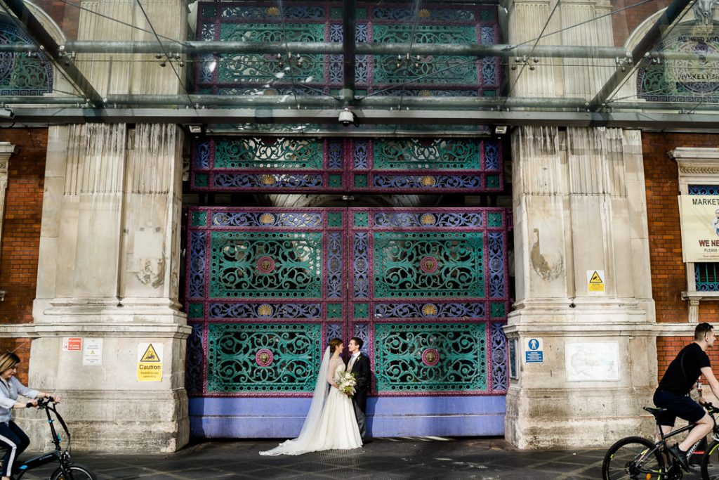 bride and groom outside colourful gates at Spitalfields market London photo by Lydia Stamps Photography