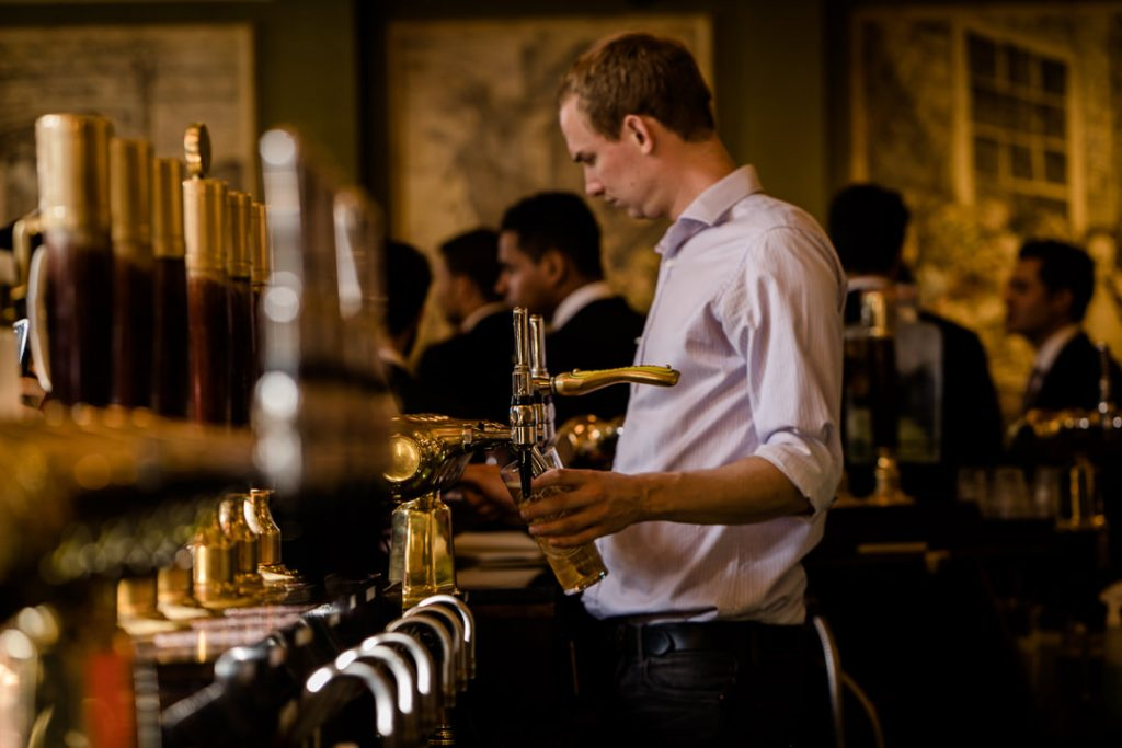 barman pulls a pint at a London pub wedding in Smithfields photo by Lydia Stamps Photography