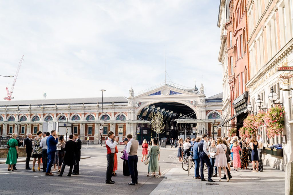 wedding guests spill out onto the road in front of Spitalfields market during a London pub wedding photo by Lydia Stamps Photography