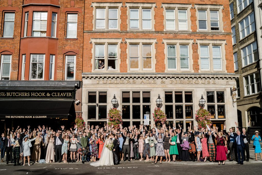 group of wedding guests outside The Butchers Hook & Cleaver pub Spitalfields, London photo by Lydia Stamps Photography