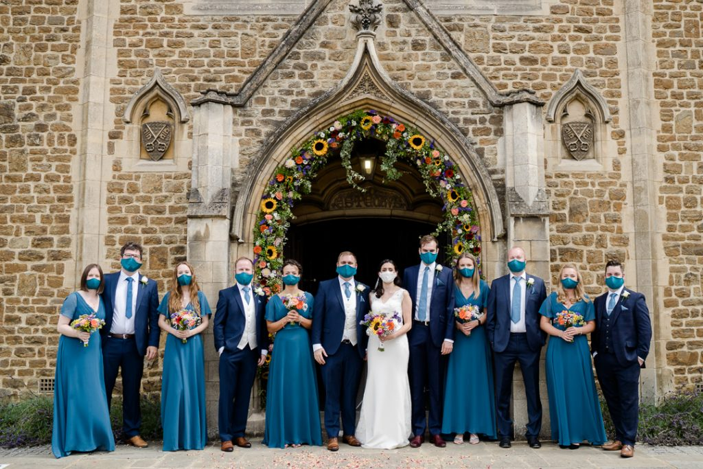 bride and groom and their wedding party outside a church all wearing masks during the covid-19 pandemic, photo by Lydia Stamps Photography