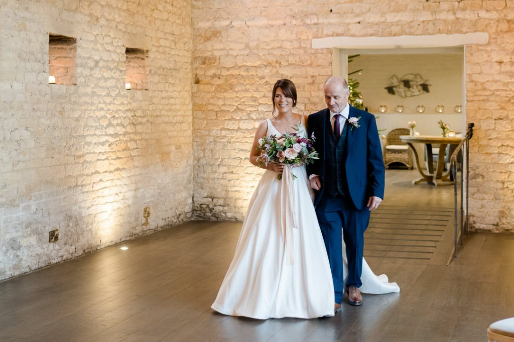 bride and her father walk down the aisle at a Lapstone Barn Christmas wedding photo by Lydia Stamps Photography