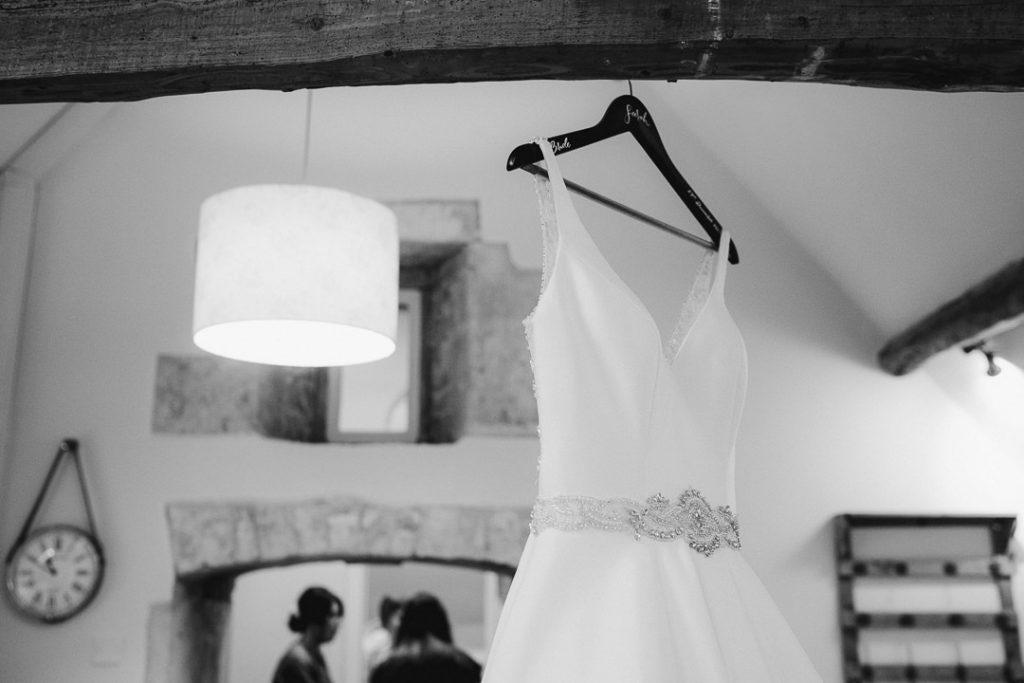 wedding dress hanging in Lapstone Barn bridal prep room photo by Lydia Stamps Photography