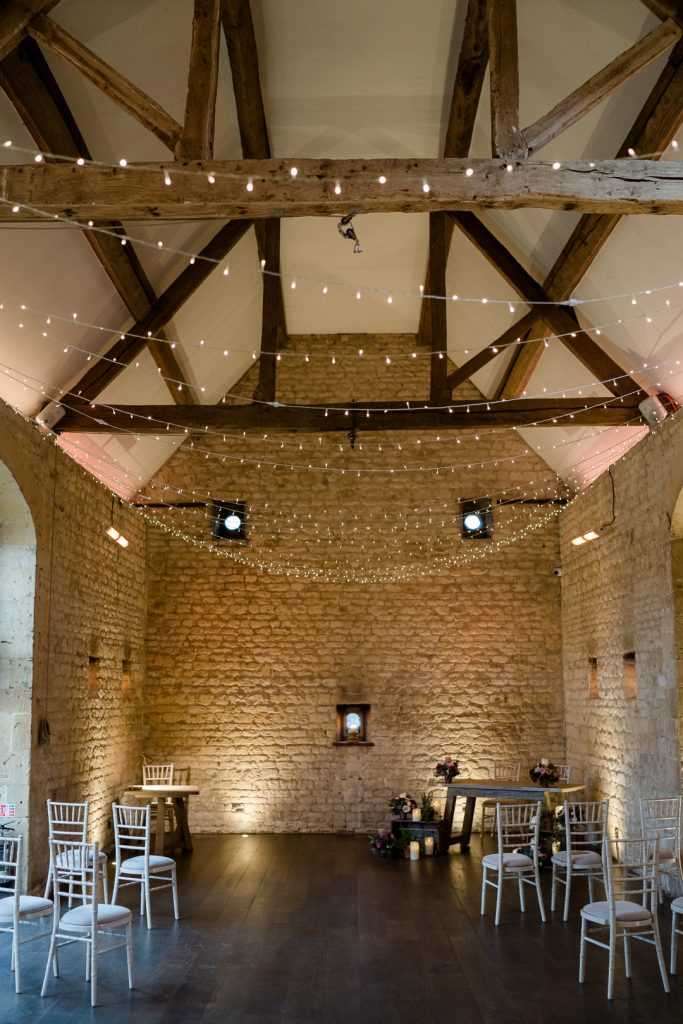 Lapstone Barn ceremony area dressed with fairy lights for a winter micro wedding photo by Lydia Stamps Photography