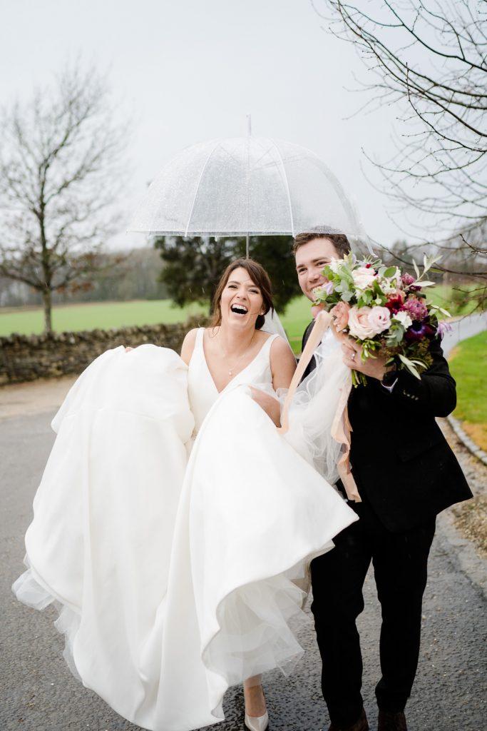 Bride and groom walk under umbrella on rainy wedding day at Lapstone Barn