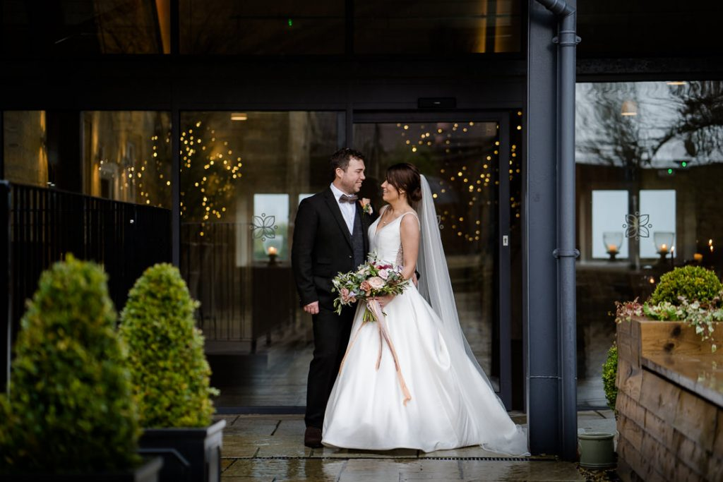 Bride and groom in the courtyard of Lapstone Barn Cotswolds wedding venue photo by Lydia Stamps