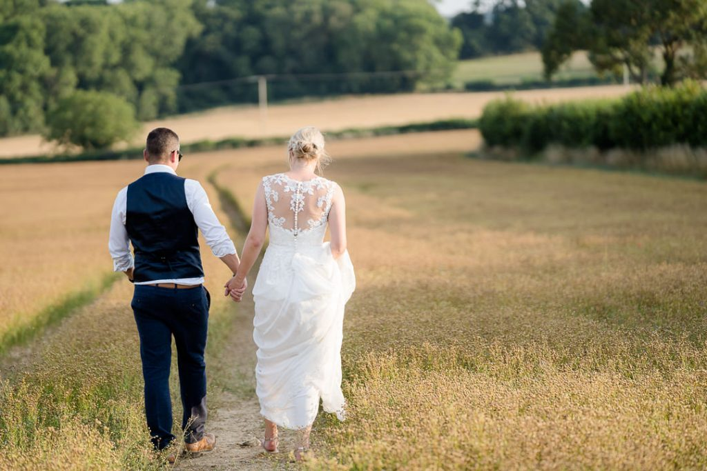 bride and groom walking through a field at sunset in the Wiltshire countryside photo by Lydia Stamps