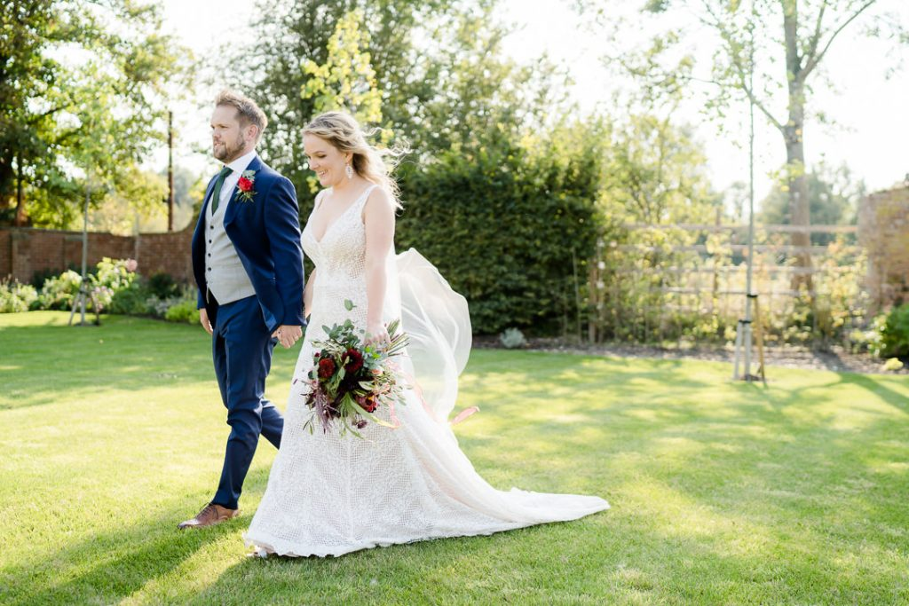 bride and groom walk through the gardens at Syrencot wedding venue near Salisbury photo by Lydia Stamps Photography