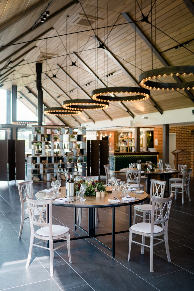 inside Syrencot main barn set for a wedding breakfast photo by Lydia Stamps Photography