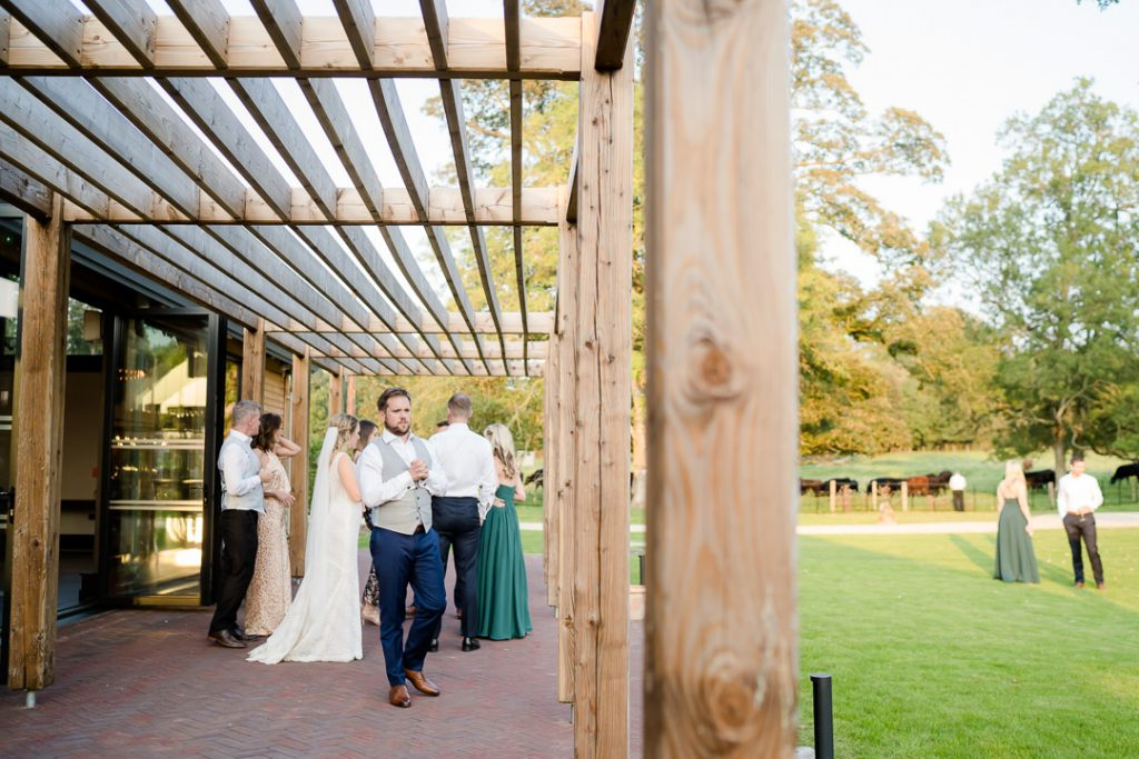 wedding guests outside on the terrace at Syrencot photo by Lydia Stamps Photography