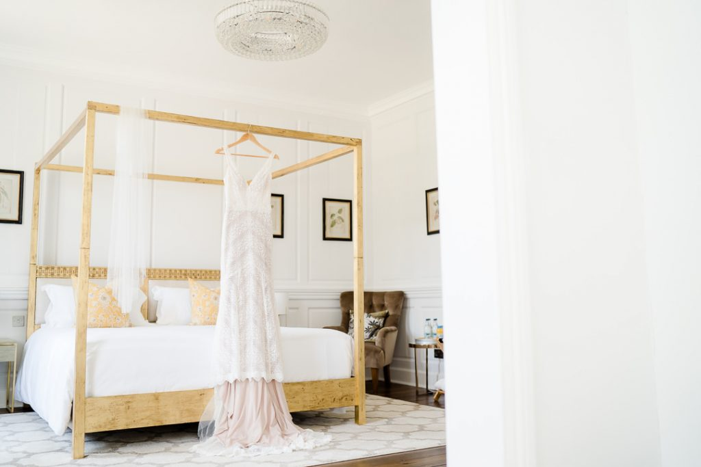 wedding dress hanging off a gold four poster bed in the bridal suite of Syrencot wedding venue near Salisbury Photo by Lydia Stamps Photography