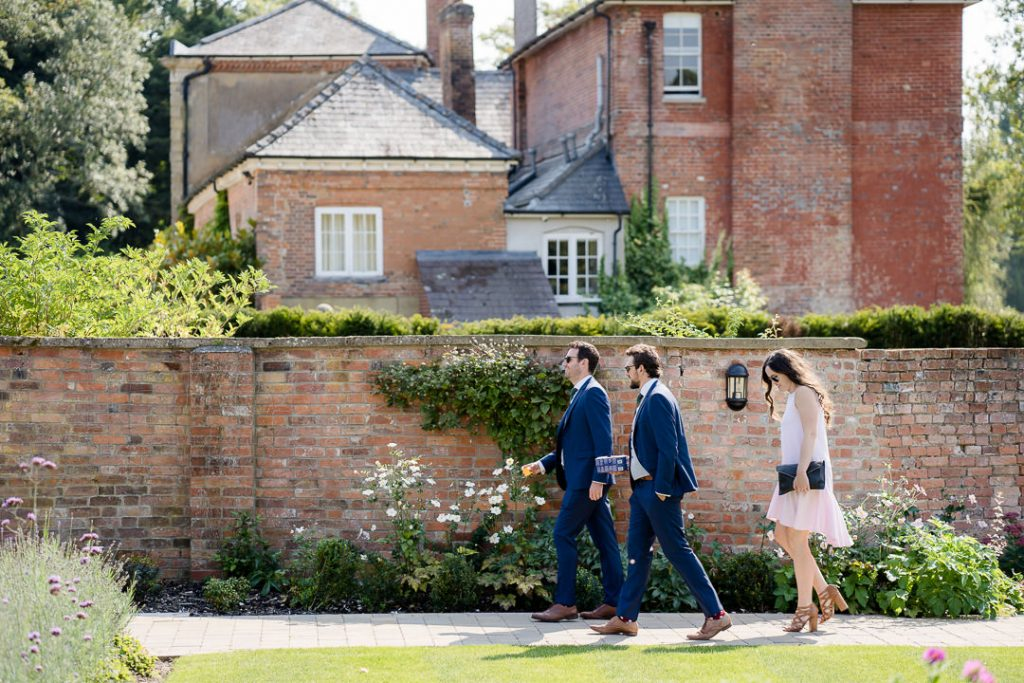 wedding guests walking through the walled garden at Syrencto Photo by Lydia Stamps Photography