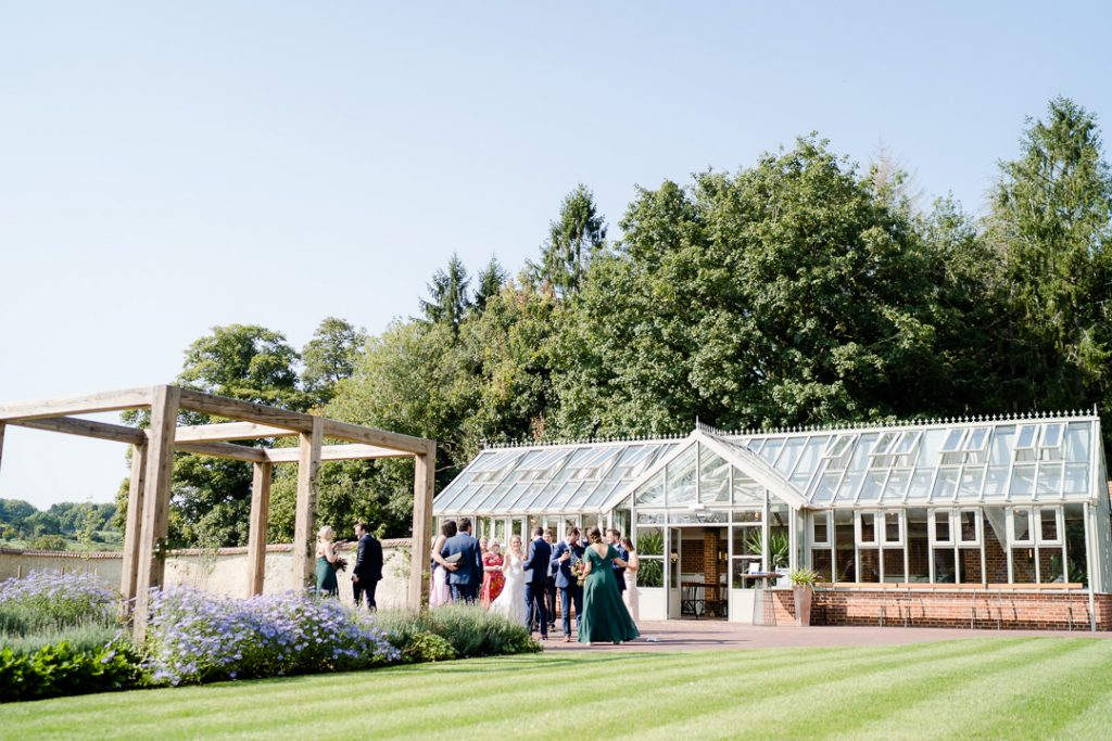 Glass house at syrencot with guests outside after a lockdown micro wedding ceremony
