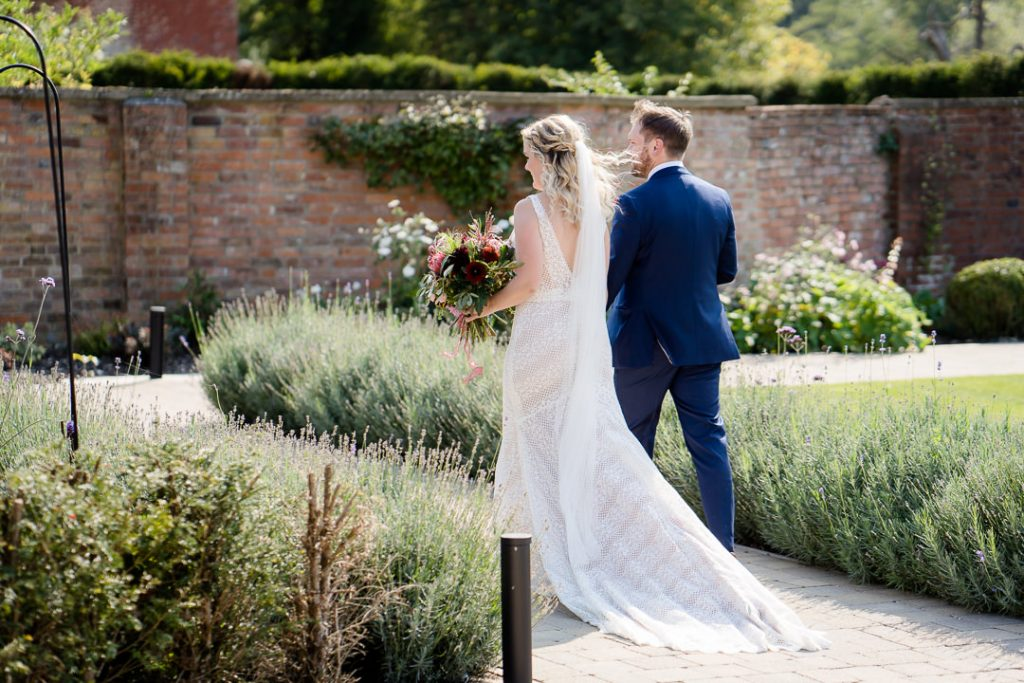 bride and groom walking through the walled gardens at Syrencot Photo by Lydia Stamps Photography