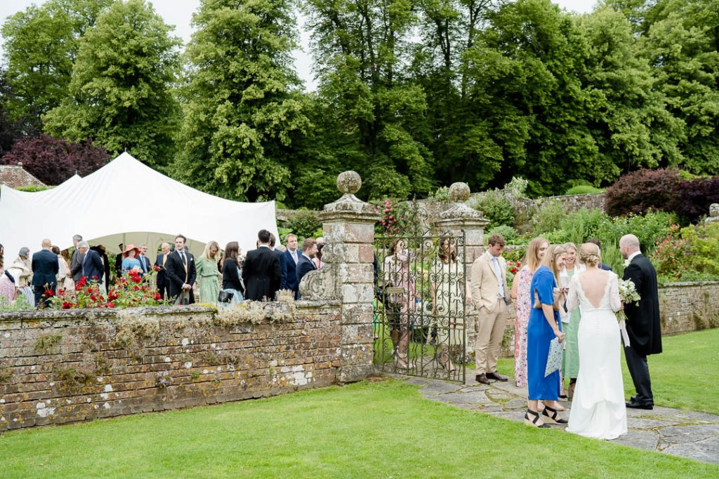 guests mingling at a wedding reception in the walled garden at Hatch House Wiltshire photo by Lydia Stamps Photography