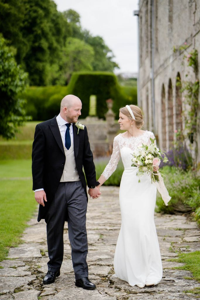 bride and groom walking at the front of Hatch House wedding venue near Salisbury Wiltshire photo by Lydia Stamps Photography