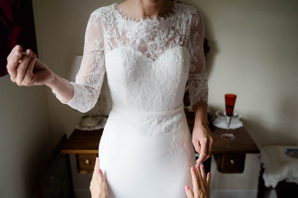 bride getting dressed in lace wedding dress from Millie Couture wedding dress shop in Salisbury photo by Lydia Stamps Photography